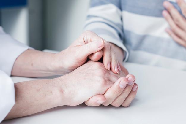 Hände des doktors, die zu einem patienten neigen