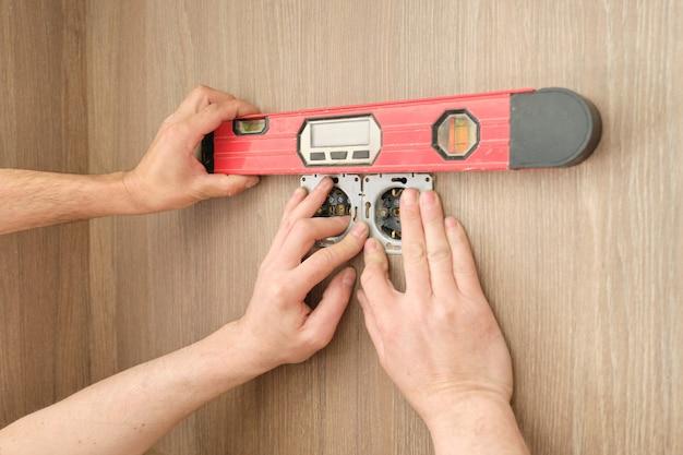 Hände des elektrikerarbeiters, der steckdose in möbeln installiert