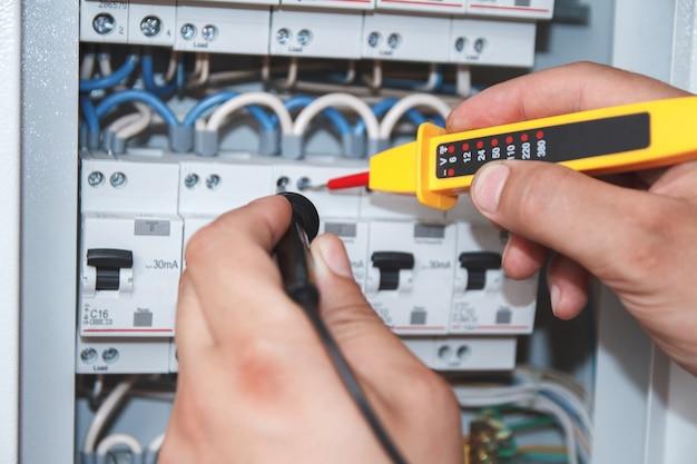 Hände des elektrikers mit multimeter-sonde an einem elektrischen schaltschrank, der sicherungskasten prüft