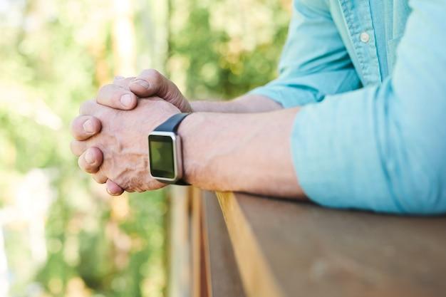 Hände des erholsamen mannes mit armbanduhr, die gegen hölzerne geländer lehnt, während zeit im landhaus im sommer verbringen