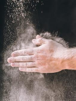Hände des erwachsenen mannes arbeiten mit mehl, dunkles foto