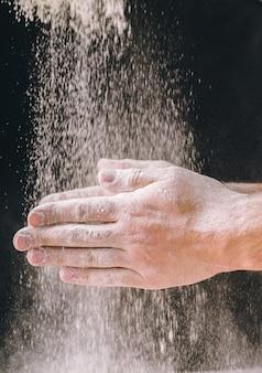 Hände des erwachsenen mannes arbeiten mit mehl