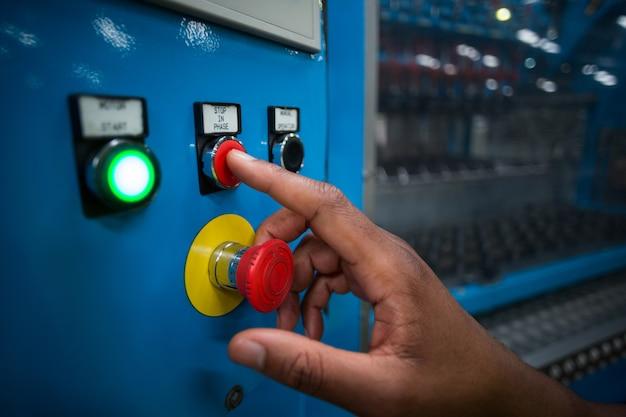 Hände des fabrikarbeiters, die einen roten knopf auf der steuerplatine drücken