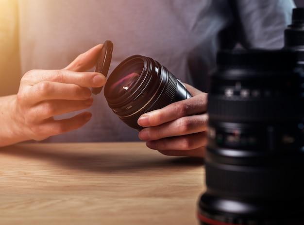 Hände des fotografen schließen das objektiv der digitalkamera am holzschreibtisch, arbeitsplatz, nahaufnahme.