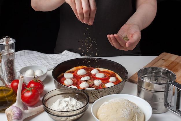 Hände des frauenkochs besprühen italienische rohe pizza.