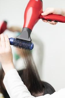 Hände des friseurs, der brünette haare des kunden mit rotem haartrockner und blauem kamm trocknet. tätigkeit in einem professionellen schönheitssalon.