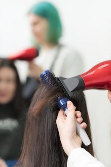 Hände des friseurs, der brünettes haar des kunden mit rotem haartrockner und blauem kamm im professionellen schönheitssalon trocknet.