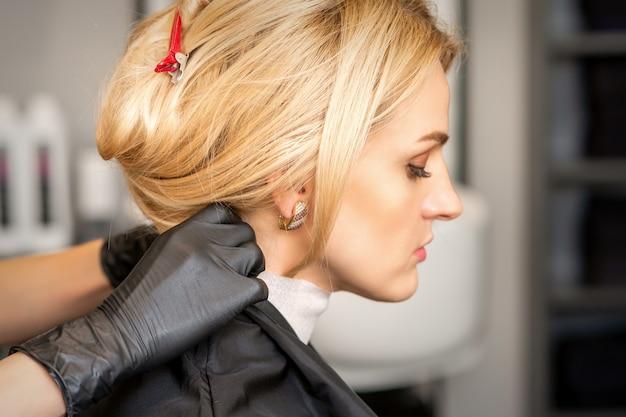 Hände des friseurs, die vorbereitung machen, bevor sie der jungen blonden frau im schönheitssalon haarschnitt geben