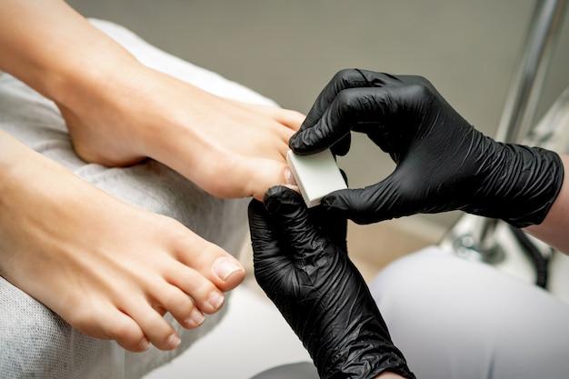 Hände des fußpflegers, der zehennagel der frau durch weißen nagelpolster im nagelstudio poliert
