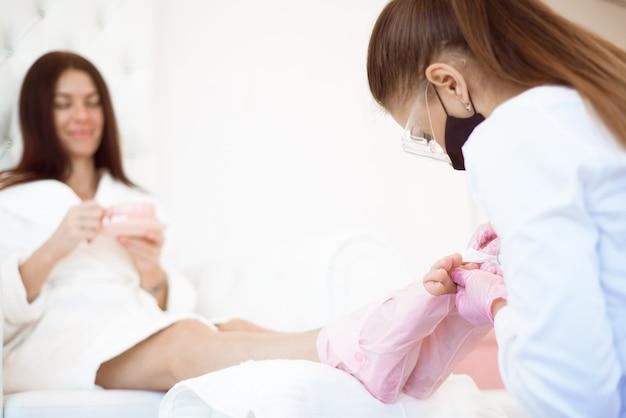 Hände des fußpflegers in gummihandschuhen, die die zehennägel mit der nagelfeile feilen.