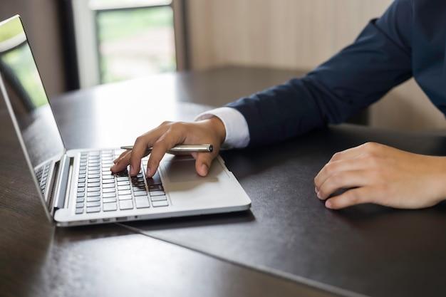 Hände des geschäftsmannes unter verwendung des notebooks am arbeitsschreibtisch im büro