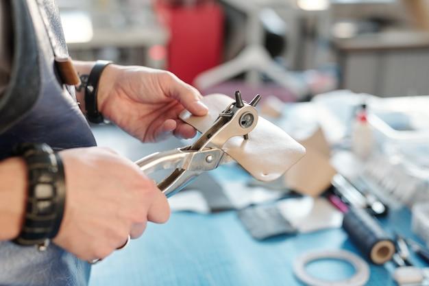 Hände des handwerkers in der schürze mit speziellem handwerkzeug, das löcher in kleines stück beige leder macht, während sie am arbeitsplatz stehen