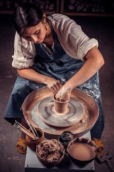 Hände des handwerkskünstlers, der handwerk, keramik, bildhauer aus frischem nassem ton auf töpferscheibe herstellt, modellierung von töpferei auf der töpferscheibe