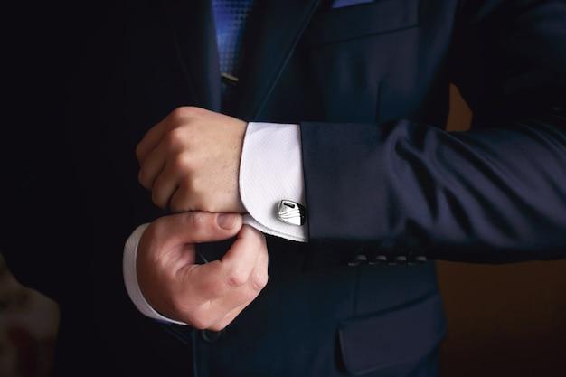 Hände des hochzeitsbräutigams, der sich im anzug fertig macht