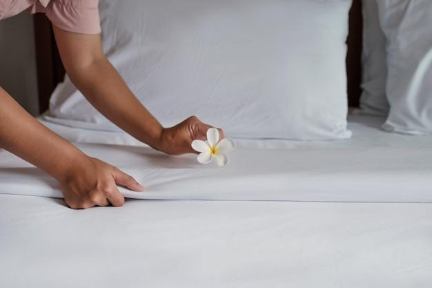 Hände des hotelmädchens, das das bett im luxuriösen hotelzimmer für touristische reisen bereit macht.