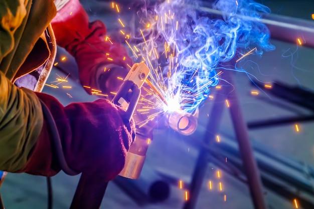 Hände des industriearbeiters mit schutzhandschuhen, die metallstahlteil schweißen