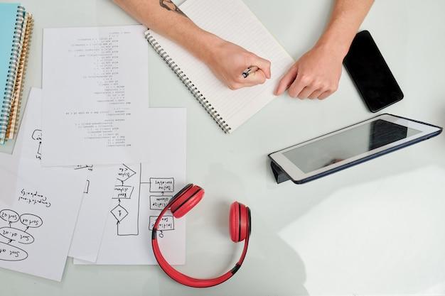 Hände des jugendlichen programmierers, der strukturdiagramm zeichnet, bevor mit dem codieren begonnen wird, ansicht von oben