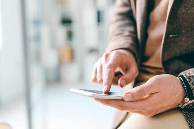 Hände des jungen eleganten geschäftsmannes, der auf smartphonebildschirm zeigt oder durch informationen scrollt