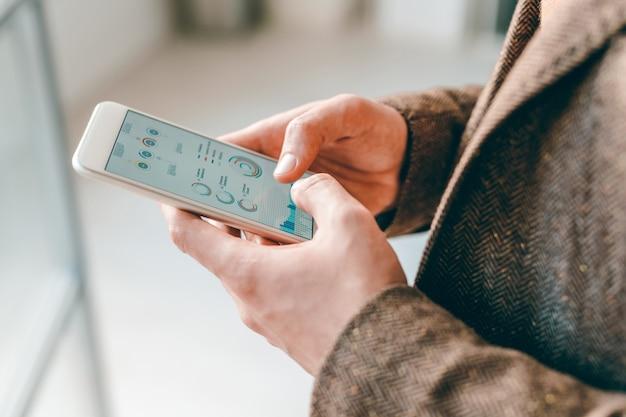 Hände des jungen eleganten ökonomen, der während der analyse durch finanzdaten im smartphone blättert
