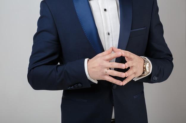 Hände des jungen erfolgreichen geschäftsmannes im smoking