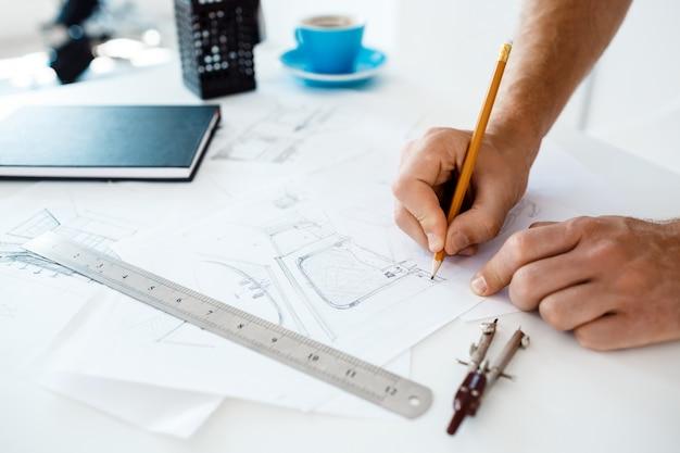 Hände des jungen geschäftsmannes, der bleistift und zeichnungsskizze am tisch hält. weiße moderne büroeinrichtung