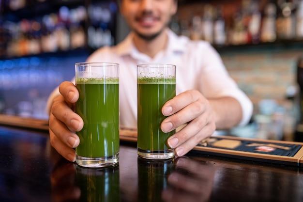 Hände des jungen kellners oder des barmanns, der zwei gläser des grünen gemüsecocktails auf theke stellt, während kunden des cafés dienen