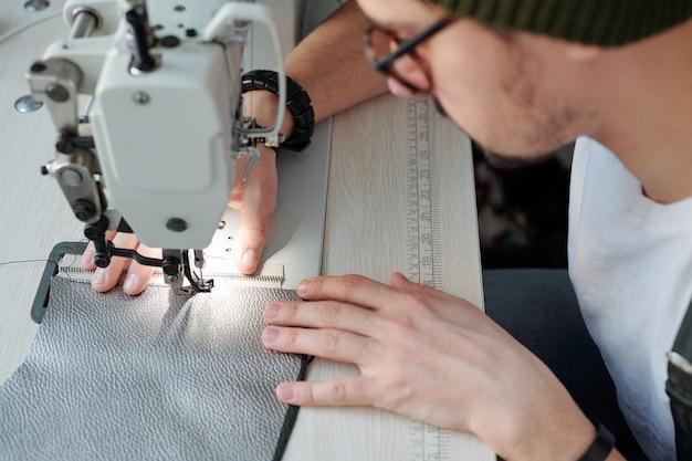 Hände des jungen lederarbeiters, der reißverschluss und ein stück leder zusammennäht, während sie sich über elektrische maschine in werkstatt beugen