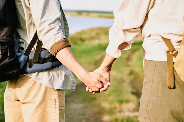 Hände des jungen liebevollen paares mit rucksäcken, die auf landstraße stehen, während reise oder wandern in natürlicher umgebung durch see haben