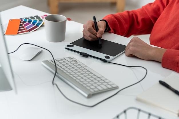 Hände des jungen männlichen freiberuflers mit dem stift, der fotos im grafiktablett retuschiert, während er am schreibtisch sitzt