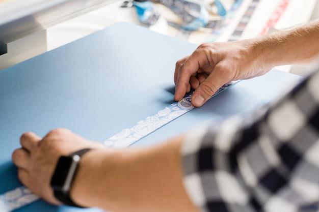 Hände des jungen meisters, der haustierhalsbandwerkstück auf spezielle ausrüstung setzt, um verzierung zu drucken, während zu hause arbeiten