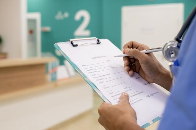 Hände des jungen mischlingsprofis mit stift, der medizinische notizen im dokument während der arbeit im krankenhaus macht
