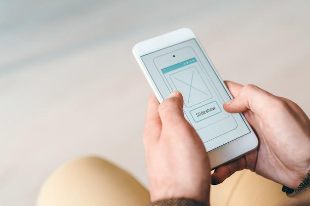 Hände des jungen mobilen geschäftsmannes, der durch diashow im smartphone bei der arbeit scrollt oder schaut