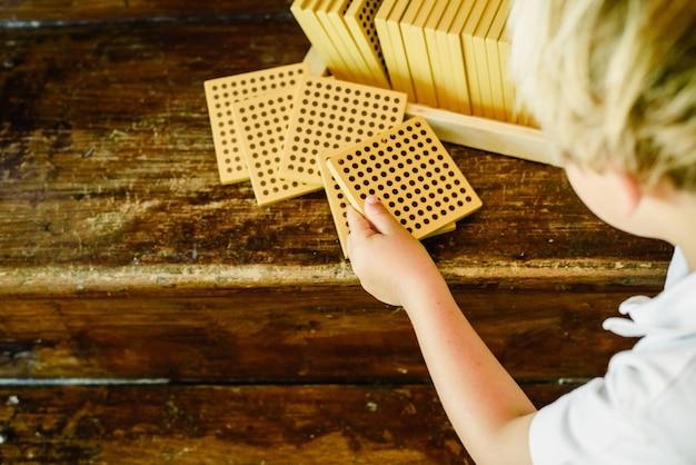Hände des jungen zählende würfel auf hölzernem hintergrund in montessori-klassenzimmer manipulierend