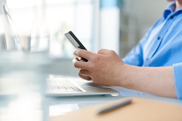 Hände des jungen zeitgenössischen studenten oder angestellten, der smartphone über arbeitsplatz während des schreibens hält