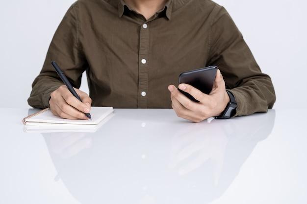 Hände des jungen zufälligen geschäftsmannes mit smartphone und stift, die arbeitsplan im notizbuch durch schreibtisch aufschreiben