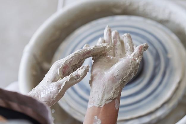 Hände des keramikers mit ton bedeckt nach der arbeit an der töpferscheibe