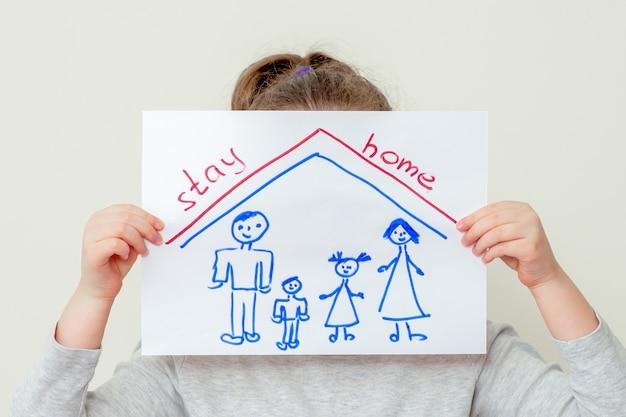 Hände des kindes, das ein bild der familiensilhouette unter dem dach hält und die worte stay home bedecken ihr gesicht auf gelbem hintergrund kinder im quarantänekonzept.