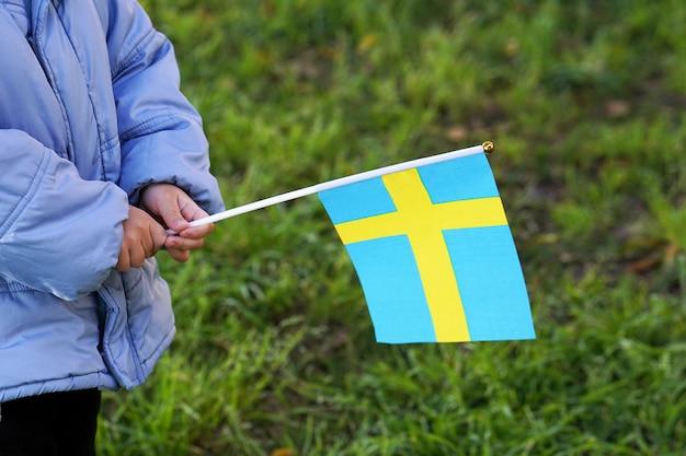 Hände des kleinen jungen halten flagge