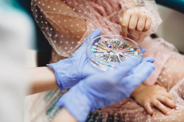 Hände des kleinen mädchens, das die instrumente für zukünftige zahnchirurgie wählt, während es in einer pädiatrischen stomatologie sitzt.