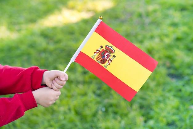 Hände des kleinen mädchens halten spanische flagge