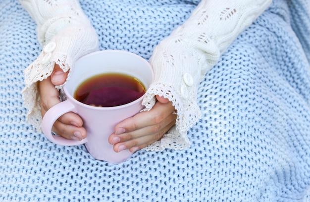 Hände des kleinen mädchens in den gemütlichen handwärmerhandschuhen, die tasse tee eingewickelt halten