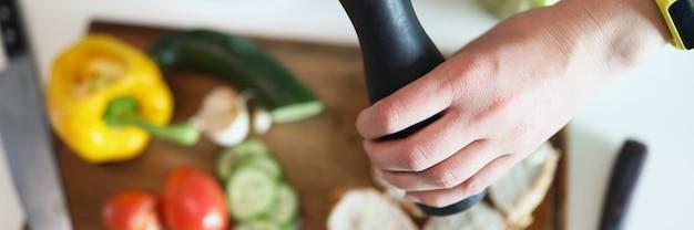 Hände des kochs, der pfeffer aus der mühle auf fleisch und gemüse gießt, nahaufnahme