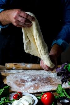 Hände des kochs italienischer koch, der pizzamann kocht hände hände, die pizzateig für pizza kochen hände kochen