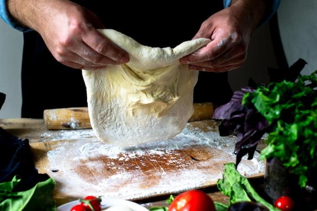 Hände des kochs italienischer koch, der pizzamannhände kocht pizzateig für pizzakochhände kocht