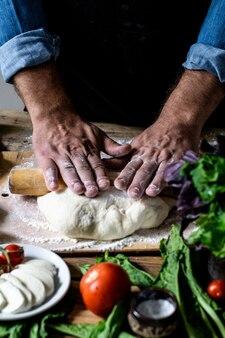 Hände des kochs italienischer koch, der teigmann kocht, hände, die pizzateig für pizza kochen