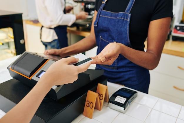Hände des kunden, der dem kassierer eine kreditkarte gibt, wenn er für die bestellung im café bezahlt
