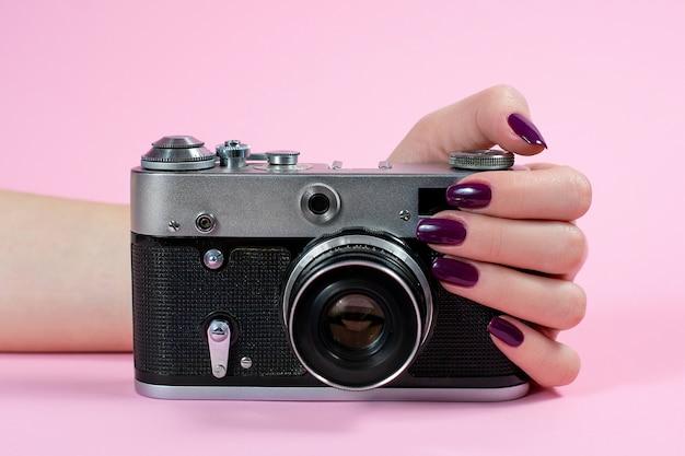 Hände des mädchens und der kamera auf einem rosa hintergrund