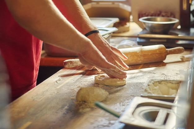 Hände des männlichen bäckers mit mehlteig, der essen auf holztisch vorbereitet.
