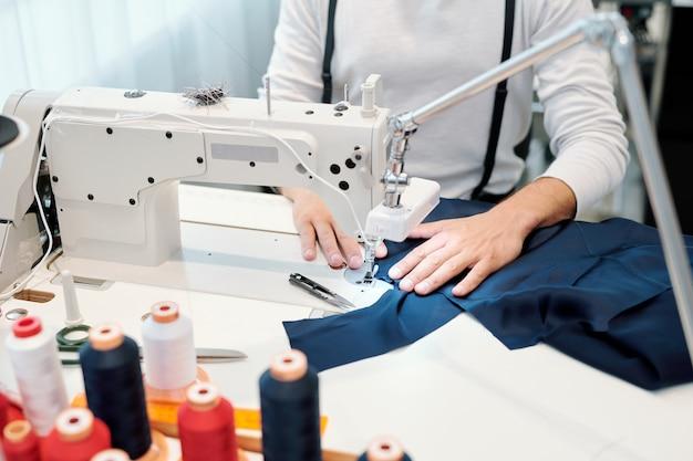 Hände des männlichen schneiders durch nähmaschine, die dunkelblaues stück textil hält, während über neuem kleidungsstück gearbeitet wird