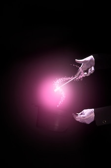 Hände des magiers, die magischen trick über einem magischen zylinder gegen schwarzen hintergrund durchführen